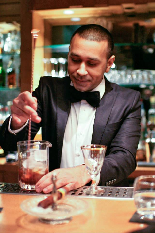 Naushad stirring liquid delight in a glass. Notice the chocolate cigar in the foreground, yes chocolate.