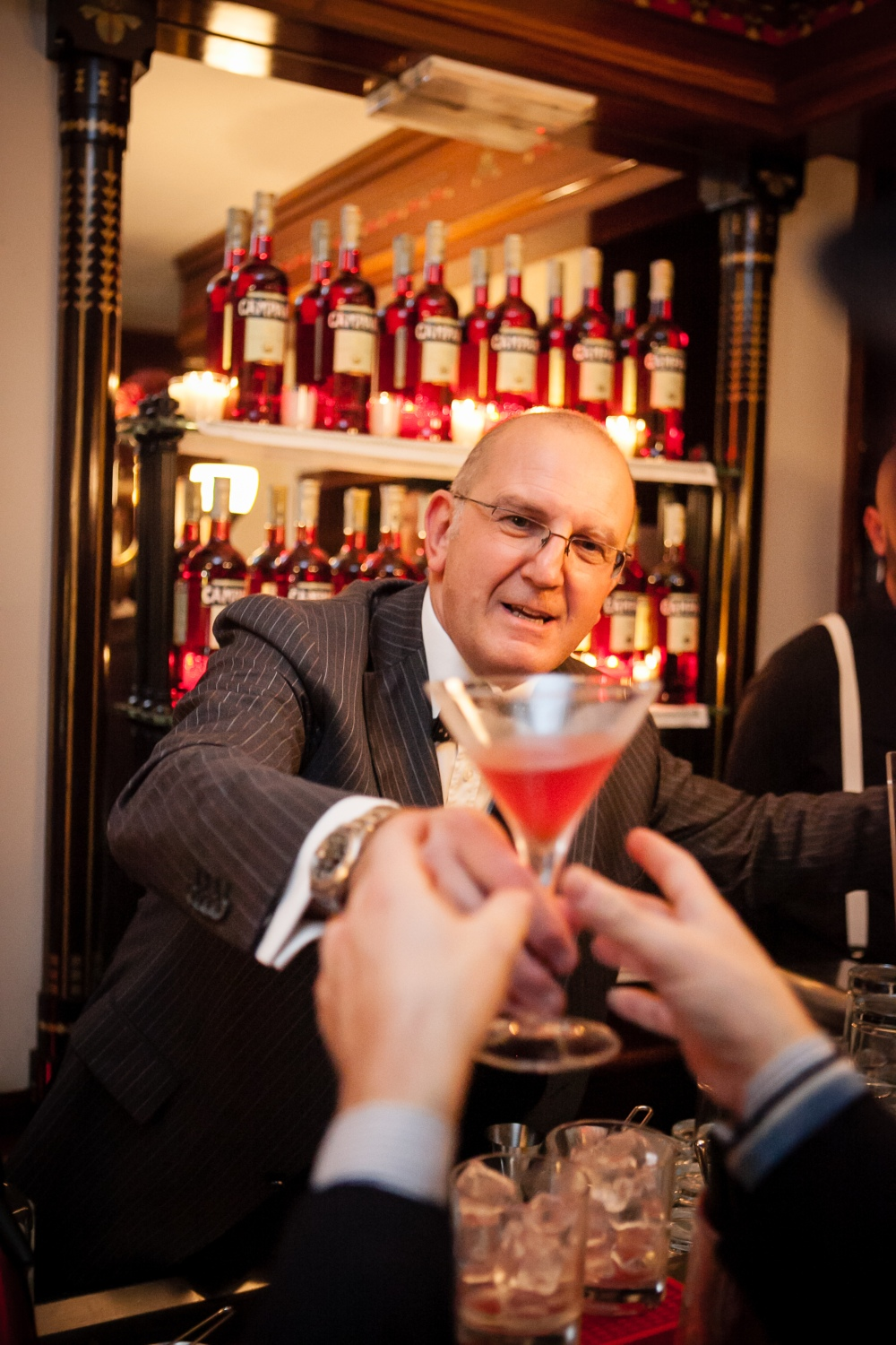 Lucca Picchi serving a Negroni to two eagerly grabbing hands